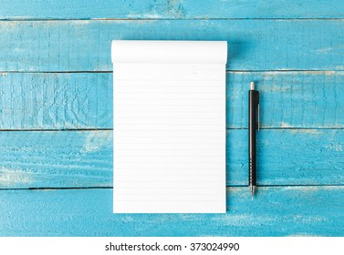 Top view of Lined note paper with pencil on blue wood table for background