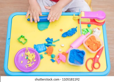 Top view of little Asian 2 years old toddler baby boy child having fun playing colorful modeling clay / play dought, cooking toys at play school, Educational toys Creative play for toddlers concept