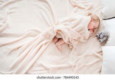 Top view of little baby covered with blanket sleeping on soft bed. She is suckling her thumb. Copy space in left side