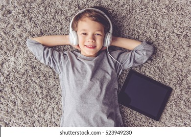 Top view of little boy in headphones listening to music, looking at camera and smiling while lying on the floor at home