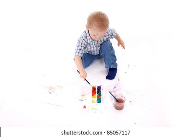 Top view of Little boy siting on floor paint