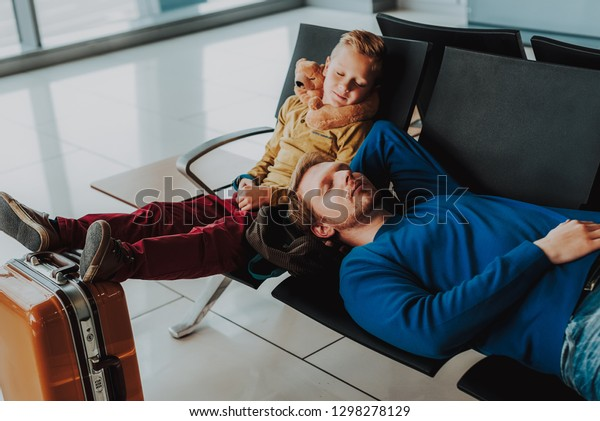 Top view of little boy sitting on bench and his dad lying on it while dreaming. They are waiting with baggage for plane in airport lobby