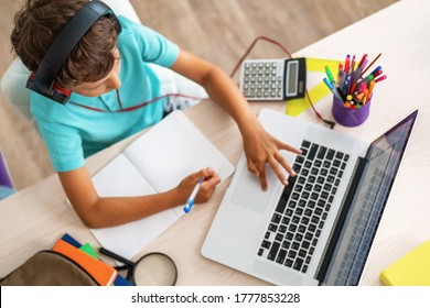 Top view, little boy using laptop and headphones studying math during his online lesson at home, social distance during quarantine, self-isolation. takes notes. E-Education Distance Home Education.