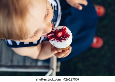 Top view of little girl eating ice cream on a swing