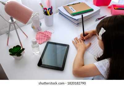 Top view of little girl studying at home with tablet and mask on table