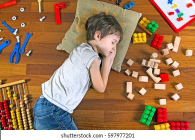 Top view of little kid with closed eyes lying on the wooden floor and many colorful toys around him.
