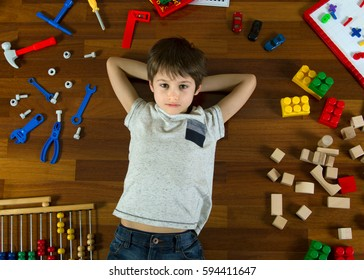Top view of little kid lying with hands behind his head on the wooden floor and many colorful toys around him.