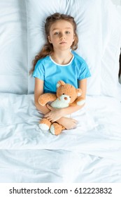 top view of little patient with teddy bear lying on bed in hospital