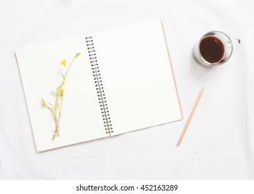 Top view of little plant with flowers on blank notebook on white fabric workspace background.