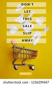 top view of little shopping trolley with paper clothes on yellow backdrop, dont let this sale slip away inscription