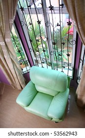 Top view of the living room with a green leather sofa by the window.