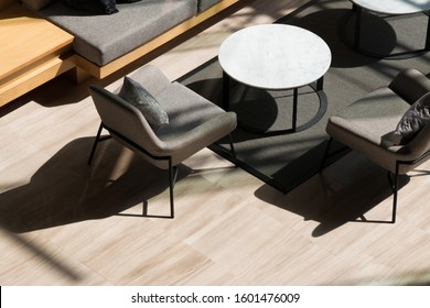 Top view of lobby lounge with long sofa, armchairs ,round tables and grey carpet on marble floor in modern residential building.