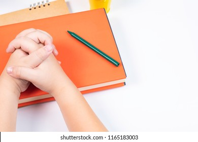 Top view or look over head boy join hand together and pay attention with the stack of books in front of him on the white background or desk /back to school concept