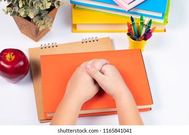 Top view or look over head boy hold hand together and pay attention with the stack of books in front of him on the white background or desk /back to school concept