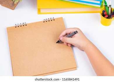 Top view or look over head boy drawing action on blank template notebook or mock up sketchbook with stack of books on the white background or desk /back to school concept