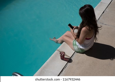 Top view looking down white Caucasian woman with long brunette hair sitting on the edge of a swimming pool with her feet in the water looking at a smartphone.  Looking at mobile phone by outdoor pool.