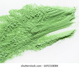 A top view of a loose green cosmetic or food powder pigment on a white background. Colorful texture. Copy space. Close-up