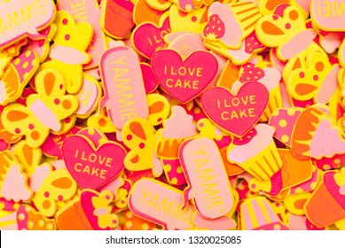 Top view of lots of candy-coloured foam stickers depicting hearts, butterflies and cupcakes. Summer or joy concept.