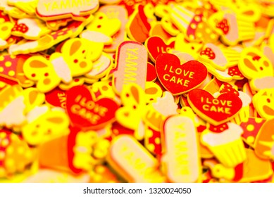 Top view of lots of colourful foam stickers depicting hearts, butterflies and cupcakes. Focus on two hearts. Summer or joy concept.