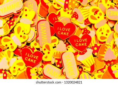 Top view of lots of colourful foam stickers depicting hearts, butterflies and cupcakes. Summer or joy concept.
