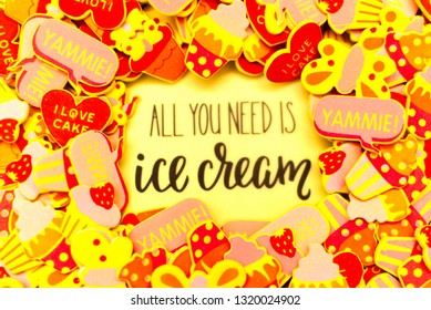 """Top view of lots of colourful foam stickers depicting hearts, butterflies and cupcakes or ice cream, surrounding a text which says """"All you need is ice cream"""". Foams in focus. Summer or joy concept."""