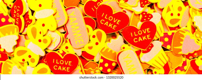 Top view of lots of colourful foam stickers depicting hearts, butterflies and cupcakes. Summer or joy concept. Facebook banner.