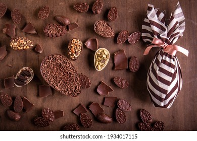 Top view of lots of mini stuffed chocolate easter eggs, cracked chocolates and a wrapped easter egg on a wooden table. - Shutterstock ID 1934017115