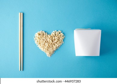 Top view I love wok takeaway noodles presentation with chopsticks, blank box and dry pasta in heart shape isolated on blue mockup