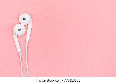 Top view Lovely Closeup of White Earphones on Pink Pastel plastic texture background. Pastel color concept, Minimal concept. Copy space. Music is my life concept. Valentine concept
