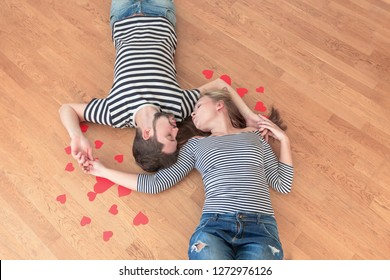 Top view of loving young couple lying on the floor and looking to each other. Toned, empty place.