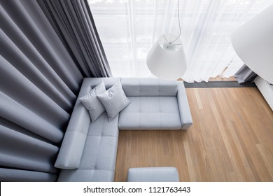 Top view of luxury living room with large corner sofa and gray window curtains