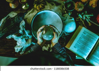 Top view of a magic ball in witch's hands above pot with poison potion.
