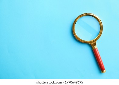 Top view of magnifier glass on light blue background, space for text. Find keywords concept