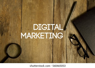 Top view of magnifier, pen, plant, eye glasses,and notebook written with DIGITALMARKETING on wooden background. A business concept.