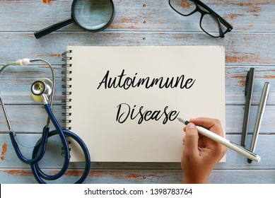 Top view of magnifying glass,glasses,stethoscope,pen and hand writing ' Autoimmune Disease ' on notebook on wooden background,