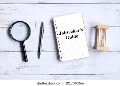 Top view of magnifying glass,hourglass,pen and notebook written with 'JOBSEEKER'S GUIDE' on white wooden background.