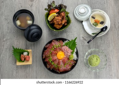 Top view of Maguro Don set with stream rice and fried chicken karaage, egg stream, soup and ice scream over the wooden table, luxury japanese food concept