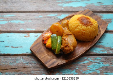 Top view of Malay traditional food called 'Nasi Minyak' with colorful rice, red chili ,spicy sauce, chicken, cucumber, carrot, and potato on the wooden plate.