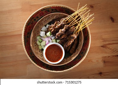 top view of malaysian food satay on the bamboo basket with the cucumber and ketupat