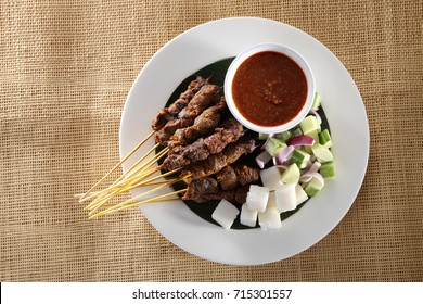 top view of malaysian food satay on the plate with the cucumber and ketupat
