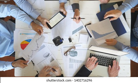 Top view male and female hands of business people planning strategy for corporate project in office. Business team sitting at table and checking financial graphs. Coworkers examining documents at desk