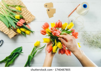 Top view male florist hands making spring bouquet using tulips at workspace with recycled wrapping materials. Learning flower arranging. Education of floristry. Flowers delivery. Selective focus