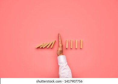 Top view of male hand stopping falling dominos in a conceptual image. Over pink background.