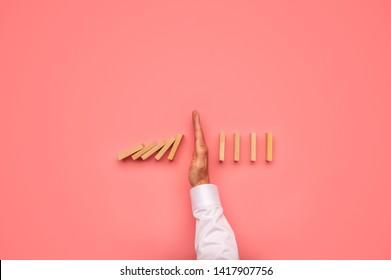 Draufsicht der männlichen Hand, die fällt Dominosteine in einem konzeptionellen Bild. Auf rosafarbenem Hintergrund.