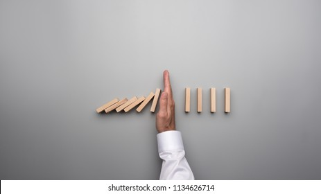 Top view of male hand in white shirt stopping falling dominos on gray desk.