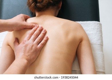 Top view of male masseur with strong hands professionally massaging scapulas and shoulders. Beautiful naked young woman with perfect skin getting back massage at spa salon.
