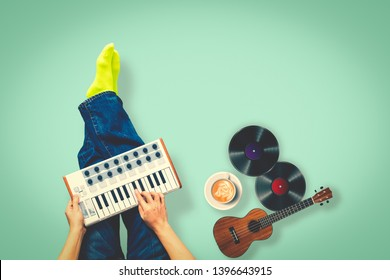 top view of male musician playing keyboard with ukulele, record, cup of coffee on green floor