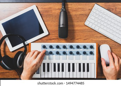 top view of male musician working on home recording studio equipment. music production concept