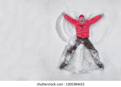 Top view of a male pensioner lying on the snow and making angel wings.Copy space.
