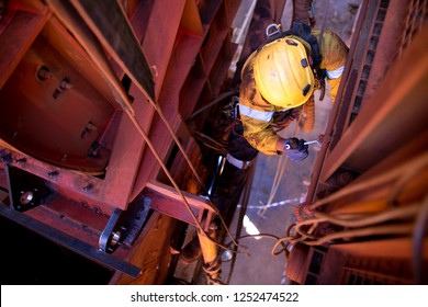 Top view of male rope access abseiler wearing safety, harness, helmet  equipment hang on rope working at height using wrench tighten bolts and nuts construction mine site, Australia